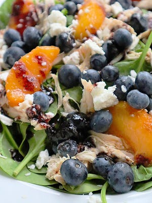 A handful of blueberries add antioxidants to a summer salad tossed with shredded chicken and peaches in a blueberry jam vinaigrette.