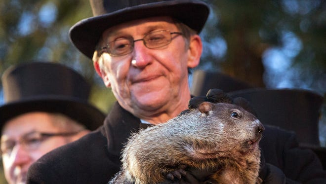 Handler Ron Ploucha holds up Punxsutawney Phil during the annual celebration of Groundhog Day on Gobbler's Knob in Punxsutawney, Pa., Tuesday, Feb. 2, 2016.