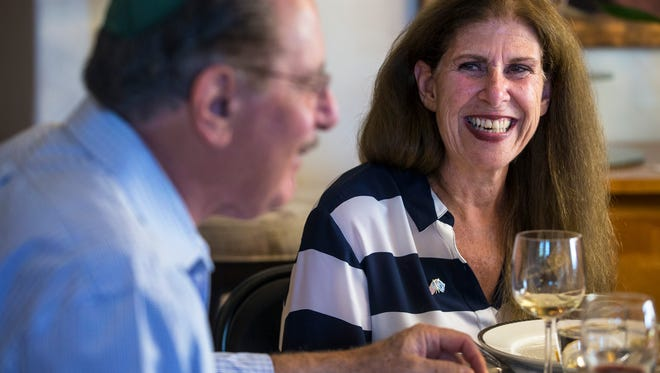 Laura Green smiles as her husband, Larry, talks about his new year wishes at their home in Sandy on Rosh Hashana. Laura supports President Donald Trump; Larry does not. However, they have found ways to put those differences aside, using the Jewish High Holidays as a way to reconcile and focus on their common ground.