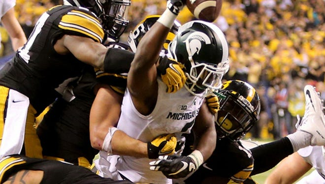 Michigan State running back LJ Scott (3) dives for the game-winning touchdown against Iowa in the Big Ten championship game.