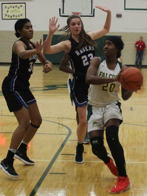 Groves senior standout Sha Carter (20) drives past Royal Oak defenders Samantha Potter (23) and Jessica Adams (31) in Friday's OAA White Division battle.