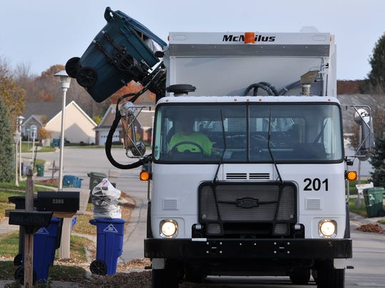 A trash truck is seen in operation on University Boulevard