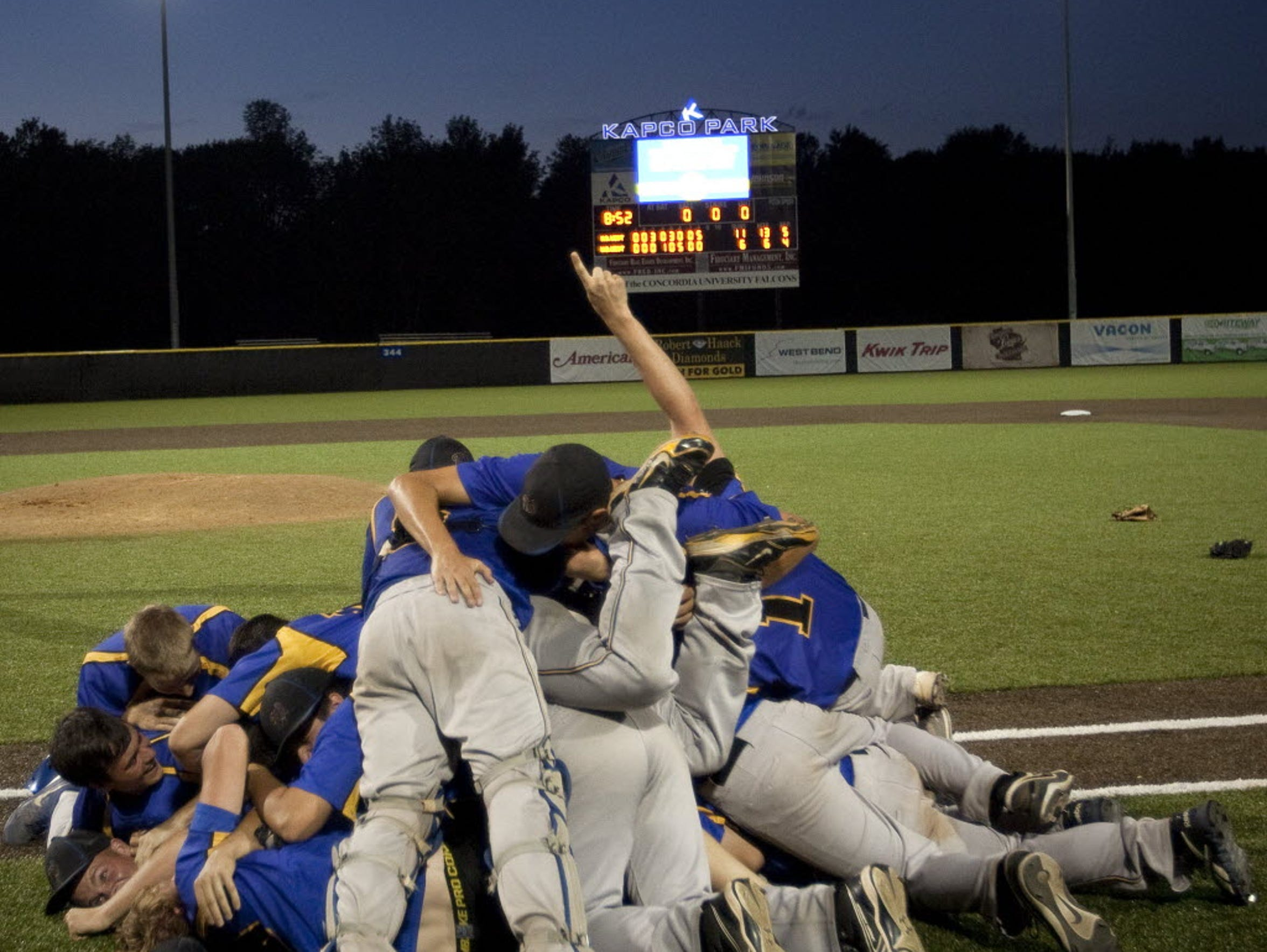 New Berlin West players dogpile on the field at Kapco