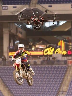A drone follows a Supercross rider during a test run inside Lucas Oil Stadium.
