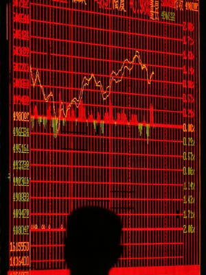An investor watches stock indexes at a securities company in Jiangsu Province, China.