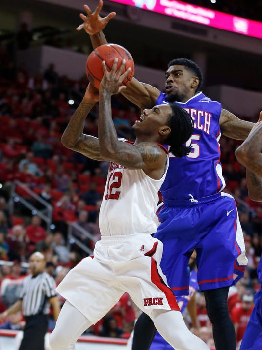 Louisiana Tech's Qiydar Davis (25) blocks the shot of North Carolina State's Cat Barber (12) during the first half of an NCAA college basketball game Tuesday, Dec. 23, 2014, in Raleigh, N.C. (AP Photo/The News & Observer, Ethan Hyman)