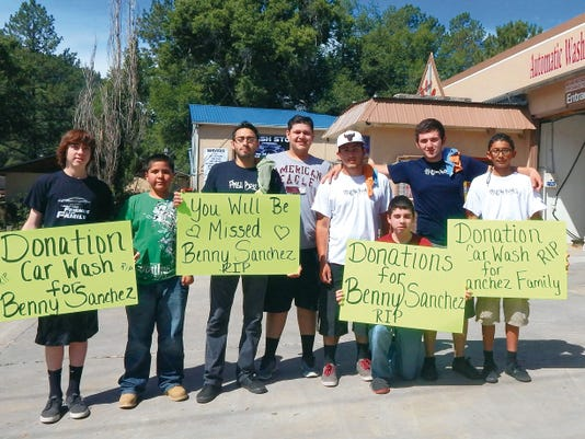 Members of the Freshboyz/Freshgirlz Car Club including Guero Aguilar, David Sida, Javier Quintana, Juan Chacon, Alexis Marquez, Juan Noriega, Kevin Chacon and Heber Ramos (third from left) hold signs during the benefit.