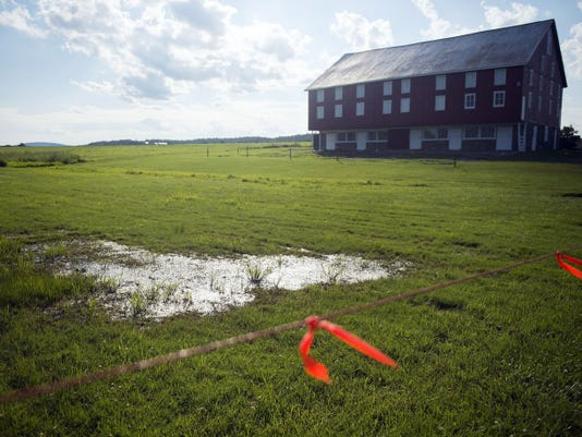 Wire and orange tape blocks off the property near some standing water at 965 Pumping Station Road, the site of the 152nd Gettysburg Civil War re-enactment events. A rainier-than-usual June prompted organizers to postpone the event until August.