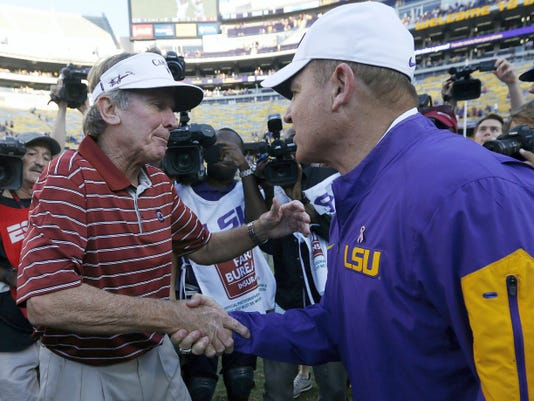 South Carolina head coach Steve Spurrier, left, and LSU head coach Les Miles shake hands after Saturday's game in Baton Rouge, La. Spurrier is retiring in the middle of his 11th season with South Carolina, the AP reported Monday.