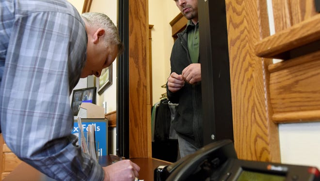 Sioux Falls City Clerk Tom Greco receives a petition from Nathan Schauer on Wednesday at Carnegie Town Hall to appeal a decision by the City Council to allow a rezone at 85th Street and Brett Avenue to go through.