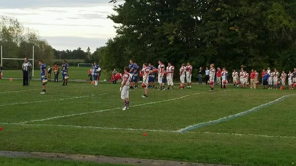 Junior-varsity football players from Fairport (in white) and Webster Schroeder stopped playing their game on Thursday night when they heard the national anthem before the start of the varsity boys soccer game on an adjacent field.