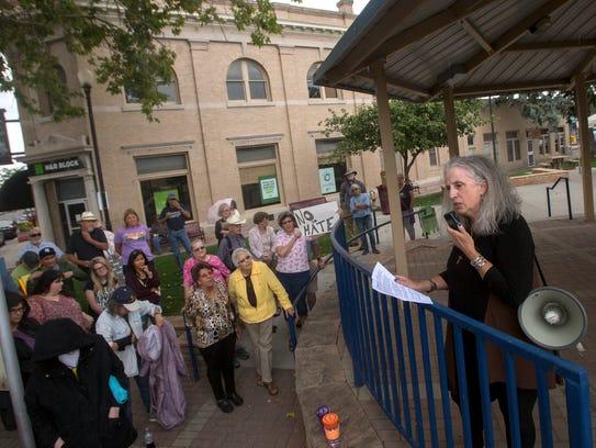 Rebecca Morgan speaks to participants in a vigil for