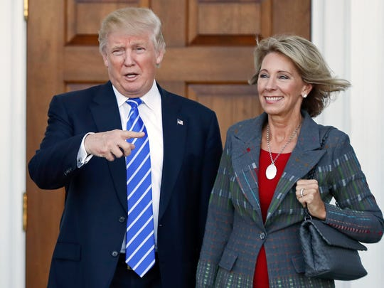 President Donald Trump and Betsy DeVos at Trump National Golf Club in Bedminster last year.