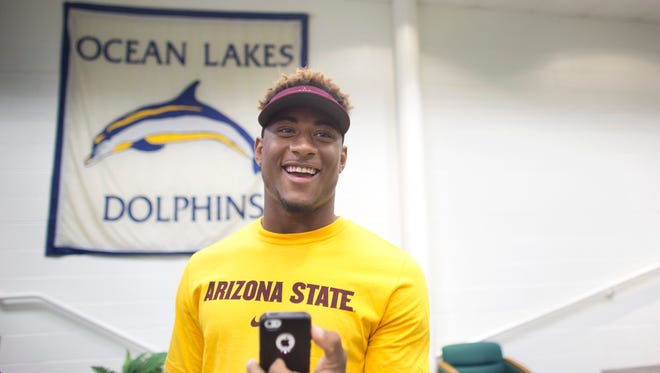 Ocean Lakes High School football player Jaason Lewis smiles on Thursday, Sept. 25, 2014, in Virginia Beach, Va., where he announced that he will be going to Arizona State. Lewis originally committed to UCLA, but de-committed a few months later.