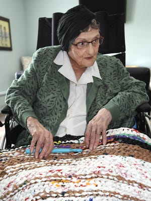 Amelia Blasich, 95, displays one of the mats she's crocheted out of plastic shopping bags. Blasich, a resident of South Lyon Gardens, has made two of the mats - each taking about four days total to piece together - for a homeless shelter up in Flint. They're used as sleeping mats so guests do not have to sleep directly on the floor.