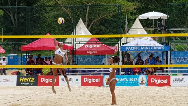 Team Guam's Tatiana Sablan lefts loose on a spike as Kendra Byrd awaits the outcome in their match against Kiribati at the X Pacific Mini Games in Port VIla, Vanuatu on Wednesday.