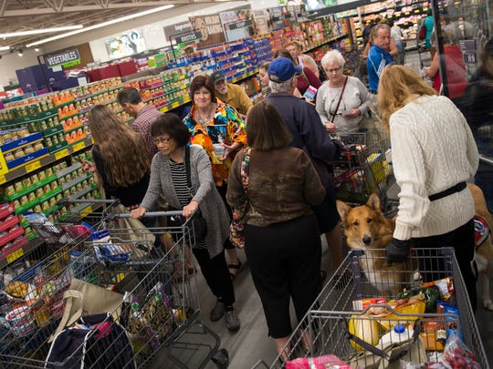 Customers shop during the grand opening of the first Aldi grocery store in Naples on Thursday, Nov. 17, 2016. The first 100 shoppers received a golden ticket, each containing Aldi gift cards ranging from $10 to $100.