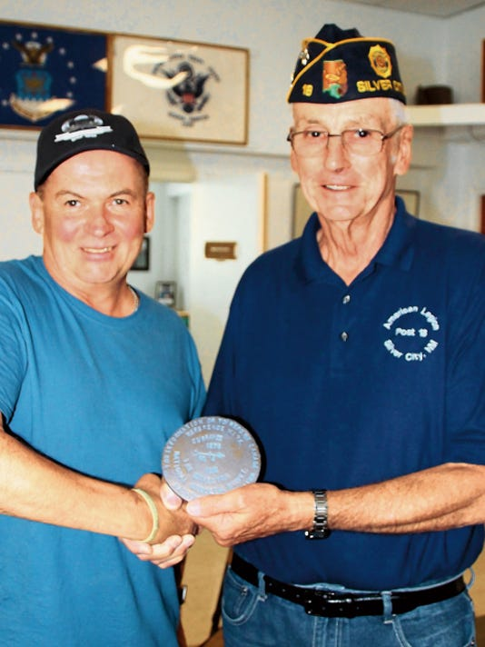 """David Ashe, also known as Irish Dave, presents to Ray Davis of American Legion Post 18, a replica plaque of the original survey plaque on top of Mount Currahee in Georgia, made famous in """"Band of Brothers,Ó where soldiers trained for WW II. Mary Alice Murphy - Sun-News"""
