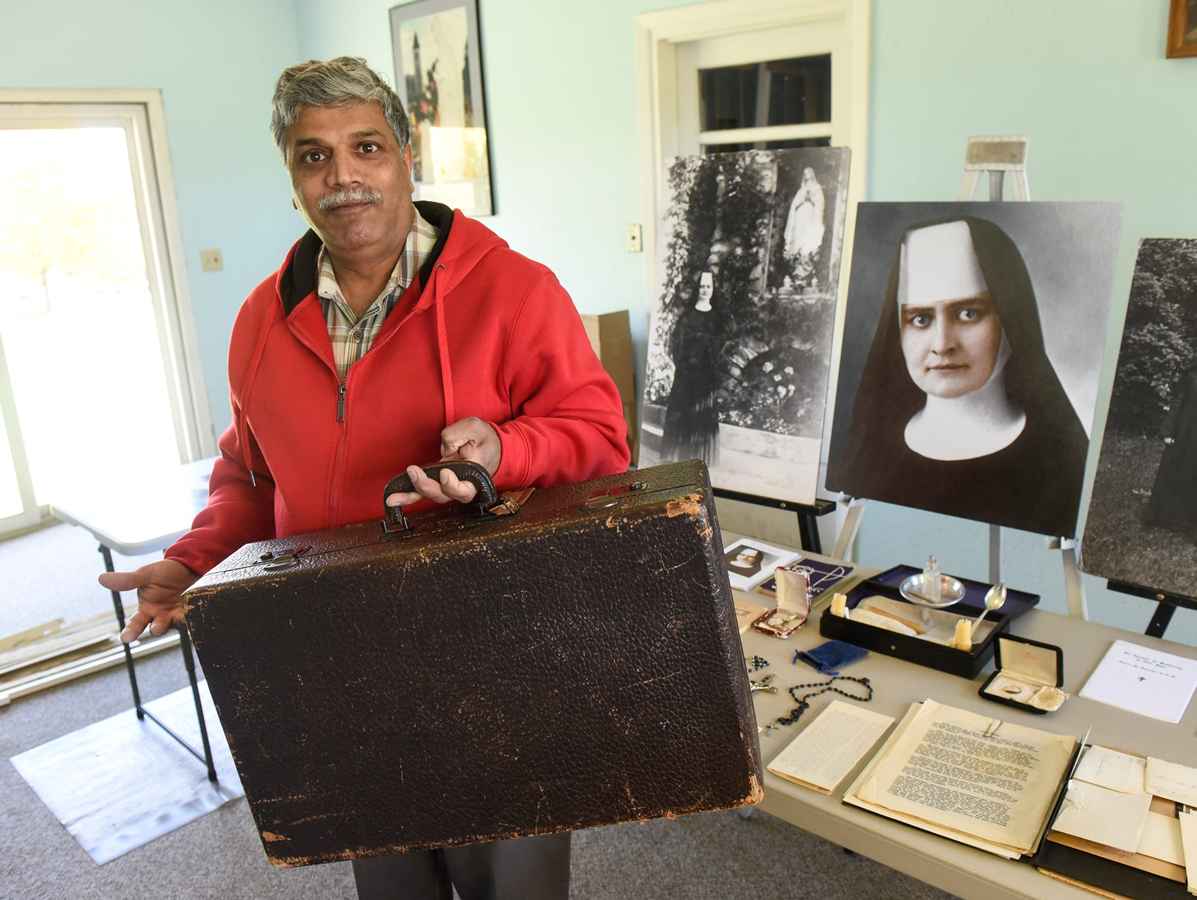 Patrick Norton holds a suitcase owned by Sister M.