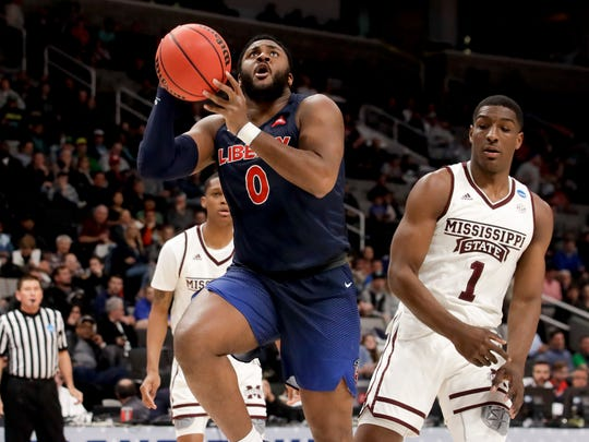 Liberty forward Myo Baxter-Bell, left, drives to the basket past Mississippi State forward Reggie Perry during the first half of a first-round men's college basketball game in the NCAA Tournament on Friday, March 22, 2019, in San Jose, Calif. (AP Photo/Jeff Chiu)