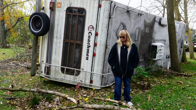 Connie Weyer stands in front of her 32-foot Coachman camper. The force of the tornado picked the camper up, lifted it over a 10-foot deck and overturned it on its side.