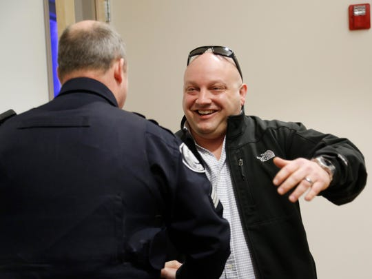 Callin Prieskorn of Waukee, right, hugs Johnston police Sgt. Kenny Agan on Tuesday, March 14, 2017, at the Johnston Police Department. The reunion came 10 years after Agan arrested Prieskorn for drunk driving. Prieskorn said he credits the arrest, his third OWI offense, as the event that triggered a change in his life and put him on the path to sobriety.