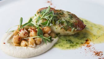 Chermoula-seared cod is served with hummus, marinated chickpeas, cilantro butter and harissa powder.