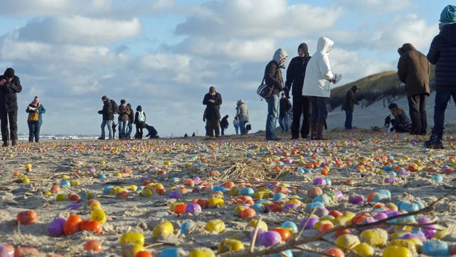 Tourists gather colorful  plastic eggs  on the beach of the German North Sea island of Langeoog, Thursday Jan. 5, 2017.