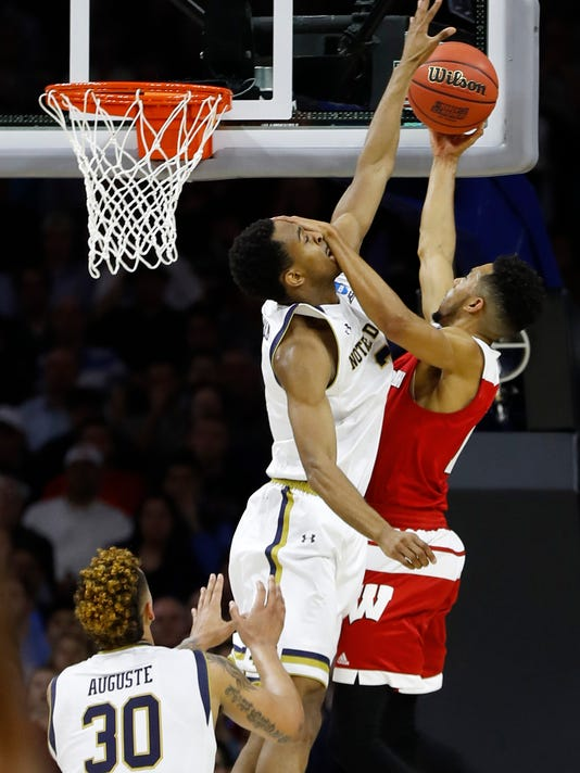 Wisconsin's Jordan Hill, right, puts a hand to the face of Notre Dame's V.J. Beachem, center, while shooting, as Zach Auguste watches during the second half of an NCAA college basketball game in the regional semifinals of the men's NCAA Tournament, Friday, March 25, 2016, in Philadelphia. (AP Photo/Chris Szagola)