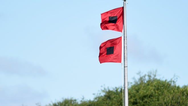 Hurricane warning flags fly in front of Wrightsville Beach Park in Wrightsville Beach, N.C., Wednesday, September 12, 2018.
