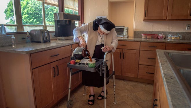 Sister Anne Marie McInnis pours her breakfast coffee in the kitchen at the Carmelite Monastery in Barrington. She arrived in Barrington at the age of 22 and has been a sister at the monastery for 60 years.