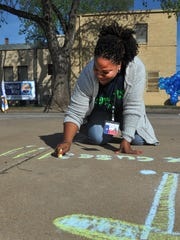 Parents as Teachers supervisor Yolanda Lewis uses chalk to write a message in 2016, during the United Way's Child Abuse Awareness Month observance. The North Texas Area United Way is kicking off their annual donation campaign.