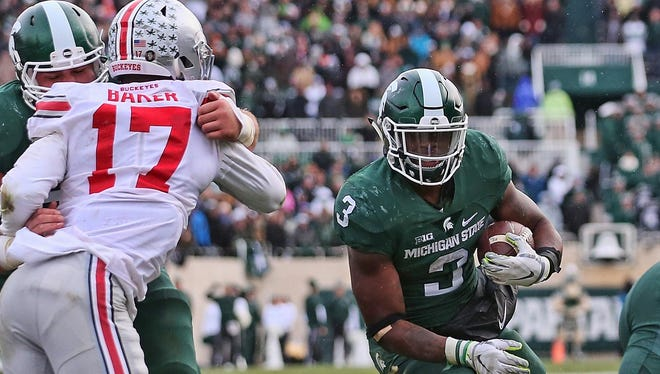 Michigan State's LJ Scott carries for the touchdown that drew the Spartans within one point of Ohio State in the fourth quarter Nov. 19, 2016.