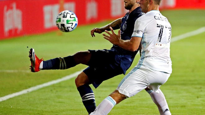 Sporting Kansas City forward Johnny Russell, left, battles Minnesota United defender Chase Gasper (77) for possession of the ball during the second half of their MLS Is Back Tournament match in Orlando Sunday night. Sporting KC, which was down to 10 players after a red card, fell 2-1 when Minnesota scored in stoppage time in its tournament opener.