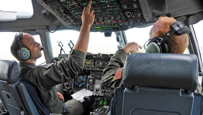 Capt. Dan Zappe (left) and Capt. Steve Churchill, C-17 Globemaster III pilots with the Air Force Reserve Command's 512th Airlift Wing at Dover Air Force Base, fly a training mission during a visit to Canadian Forces Base Trenton, Ontario, in August 2009.