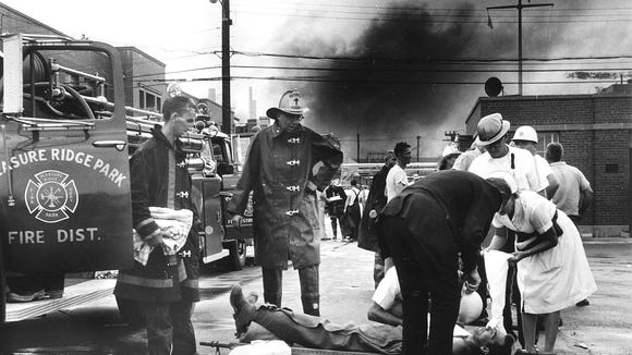 A Pleasure Ridge Park volunteer fireman hurt in the 5:45 p.m. Aug. 25, 1965, DuPont explosion is given first aid on a stretcher as smoke rises from the blast scene.