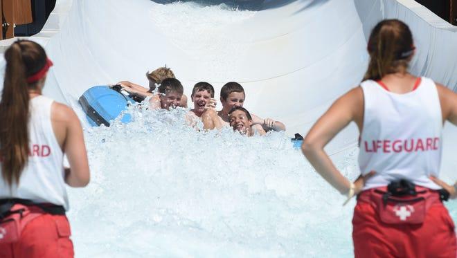 Under the watchful gaze of lifeguards,children go down a waterslide at SplashDown Beach Water Park in Fishkill.