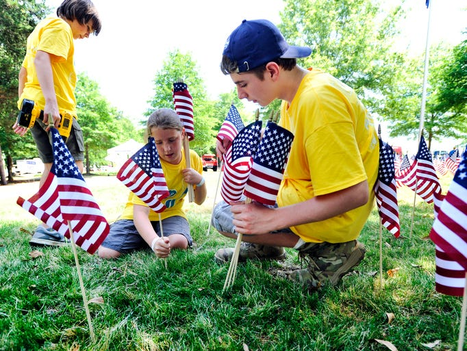 From left, Benji and Karleigh Maguire and Elijah Humes plant flags in honor of Memorial Day at Aloft 2014 in Simpsonville on Saturday, May 24, 2014.
