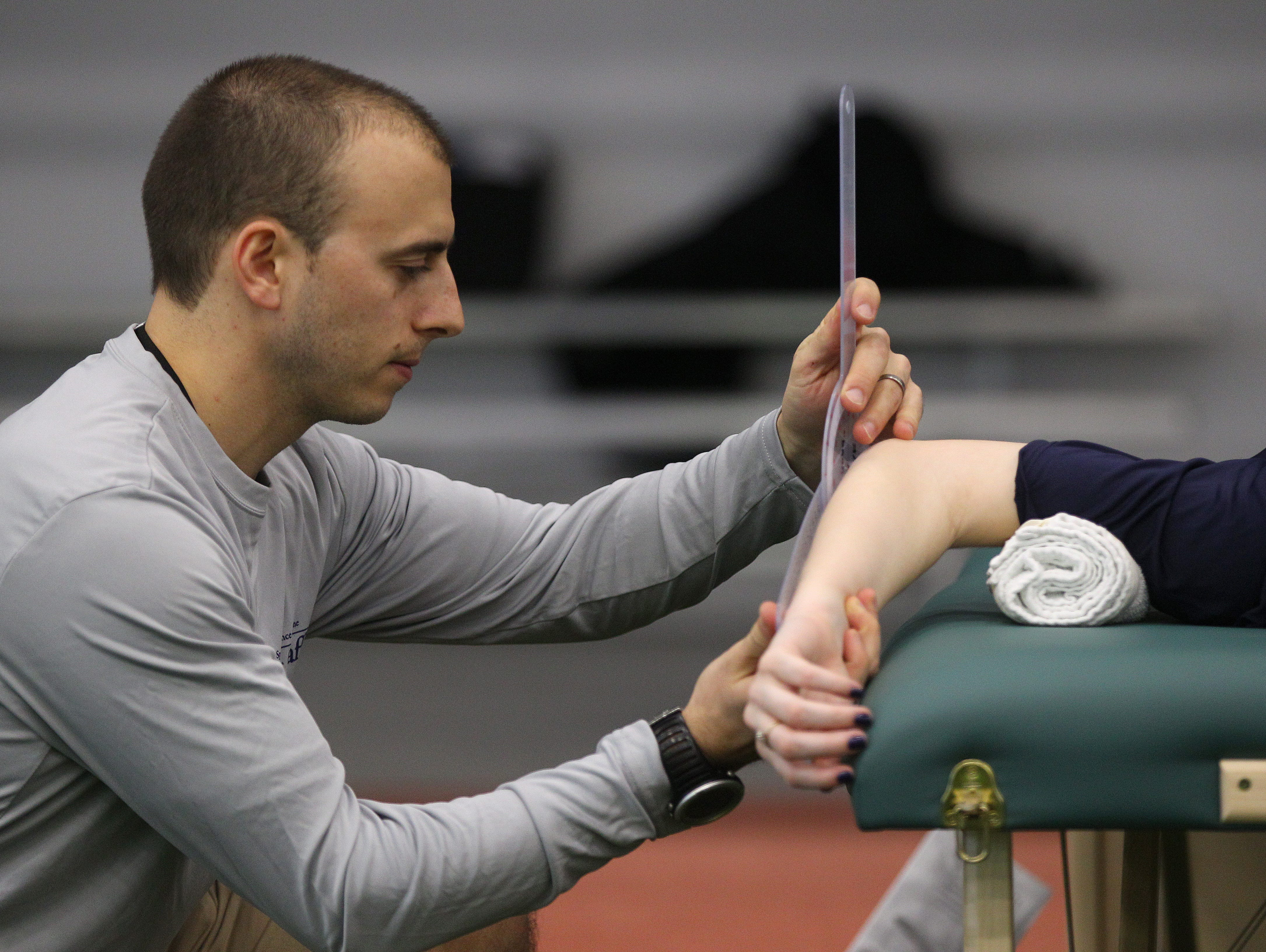 Jeremy Peters, a physical therapist with UR Medicine measures the range of motion of an athlete during the AGR Sports Combine.