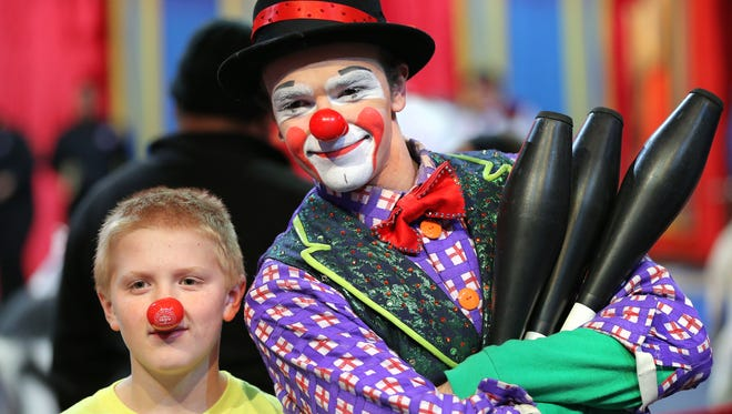Conarr Lookebill, 11 of Indianapolis, gets his photograph taken with clown Kawika Stanton during the All Access-Pre-show that offered floor access to the ultimate circus fan experience before the start of the Ringling Bros and Barnum & Bailey show held at Bankers Life Fieldhouse on Friday, Dec. 5, 2014.
