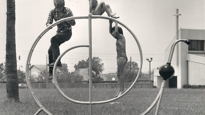 Pat McGann (left) shows Clair Giles (standing in snail) and her sister Darien (sitting on top of snail)how to climb the snail of steel at Country Club Park on April 21, 1984.