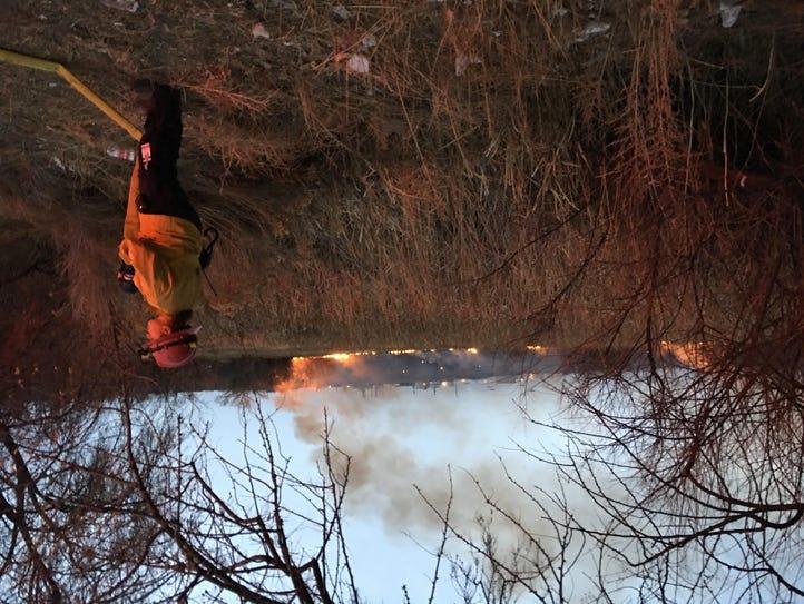 A firefighter keeps watch on a blaze burning in a field