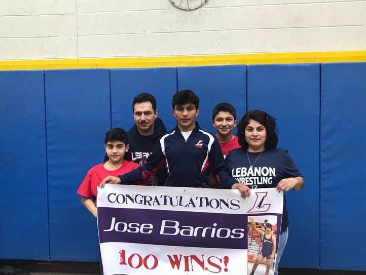 Jose Barrios, middle, celebrates his 100th career wrestling