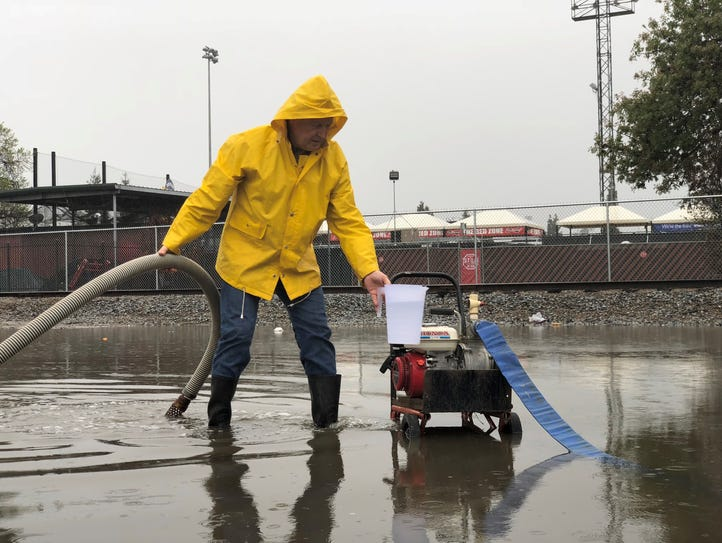 Barry Sjostrand pumps water from the flooded parking