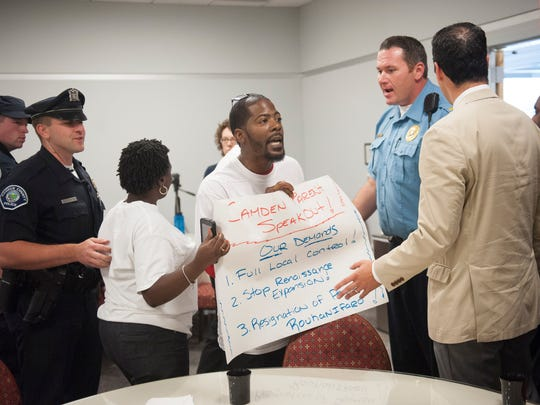 Activist Gary Frazier with Save Camden Public Schools is escorted out after confronting George Norcross and NJ Department of Education Commissioner David Hespe during a school conference at the Camden County College campus in Camden. Monday, September 22, 2015.