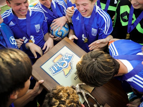Members of the Memorial soccer team kiss the trophy after the Class 2A state championship against Chesterton at Carroll Stadium in Indianapolis on Saturday. Memorial beat Chesterton 2-1.