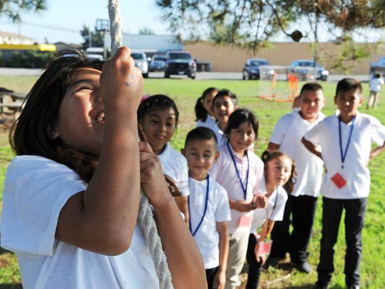 KIds line up politely behind Naxhiely Toriz, 10, as they wait to swing from a tree in the playground at L.I.F.E. in east Salinas.