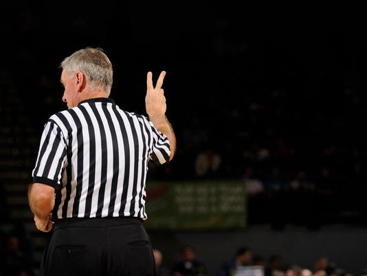 Basketball referee making hand sign
