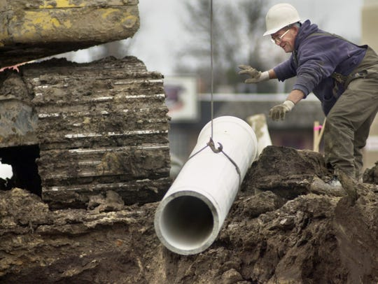 A sewer pipe is lowered into a trench box in 2006 near