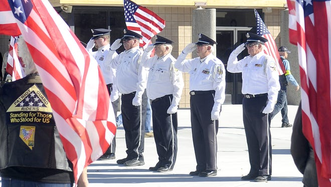Members of the Northern Nevada Veteran's Coalition Honor Guard salute during a ceremony.